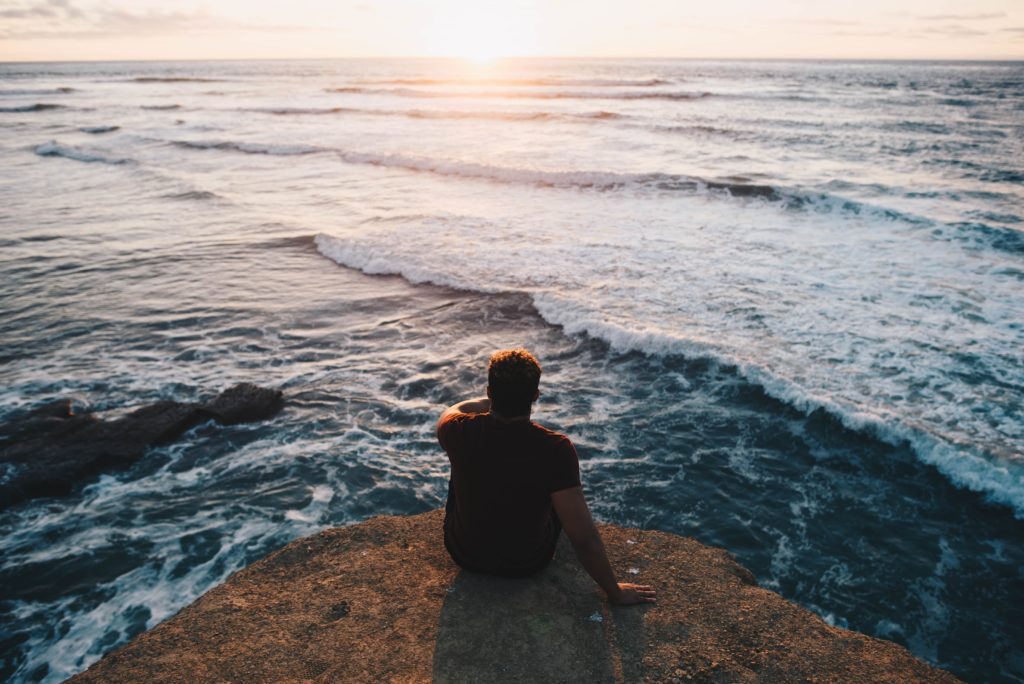 A man at the water's edge calmly contemplating the benefits of counseling and therapy